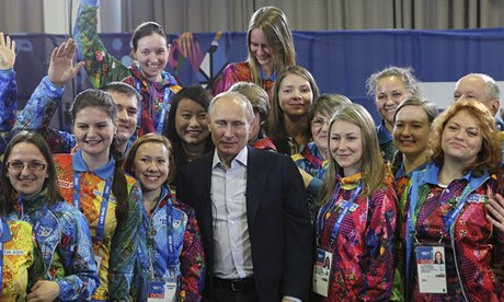 Russian president Vladimir Putin poses with volunteers after arriving in Sochi to inspect preparations for the Winter Olympics. Photograph: Sasha Mordovets/Getty